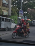 There are 4 people on this motorcycle (one child in front of the driver the other child is tucked in-between the driver and woman). Another common sight on the streets.